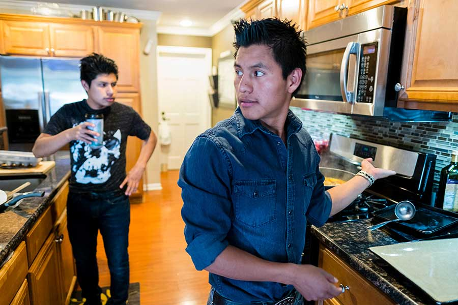Diego helps tidy up the kitchen at the house he shares with one of his brothers and six other boys in foster care.