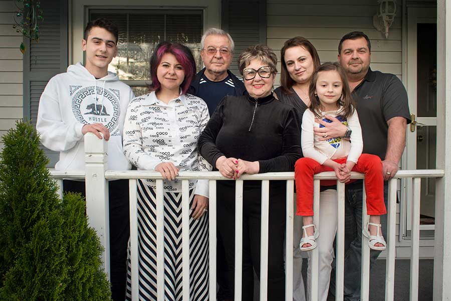 Generations on the front porch of the family home in Lansing: at center, Eugene Titov and his wife Tatyana Titova ; at left, daughter Erica Titova and her son Armen Babayan, 16; at right, son Paul and his wife Asya Vardanova with their daughter Valerie, 7.