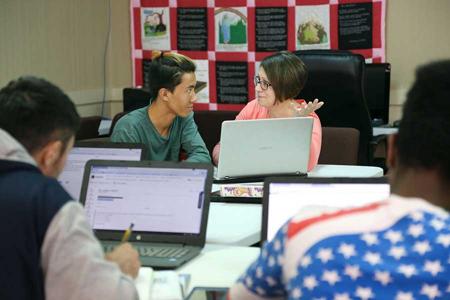 Paula Frantz, director of the Global Institute of Lansing, works with Raz on an English assignment. GIL, located in the basement of First Presbyterian Church in downtown Lansing, is a high school program for refugees who have aged out of Lansing public schools.
